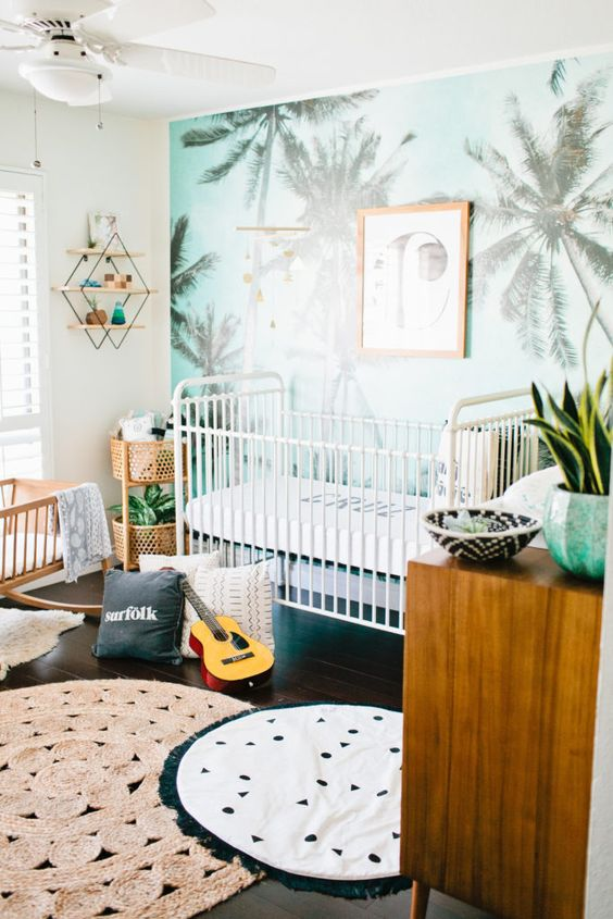 a tropical nursery for a boy, a blue palm print wall, printed rugs and warm-colored wooden furniture