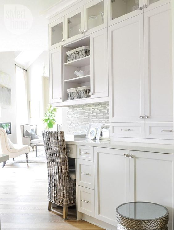 a white rustic kitchen with a built in desk and a woven chair for workign or studying