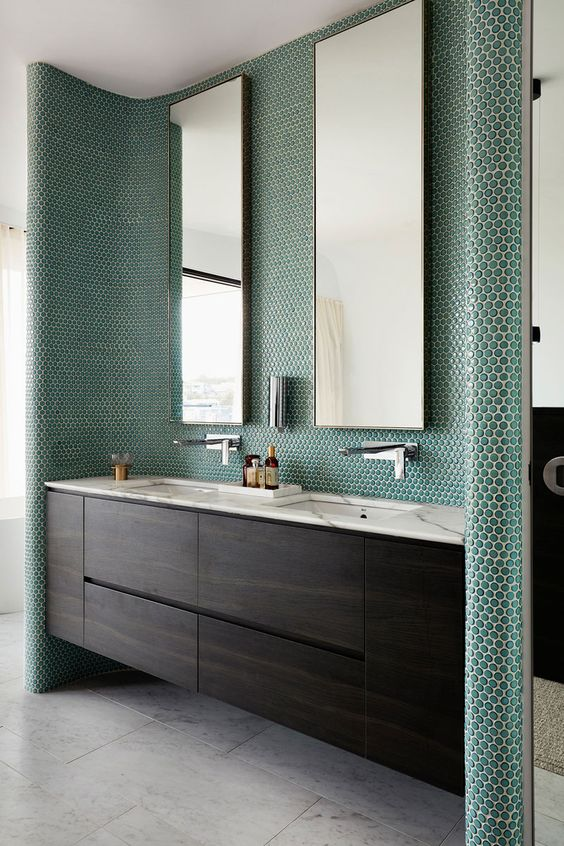 emerald penny tiles covering the sink zone highlight it and make a statement for a chic modern look