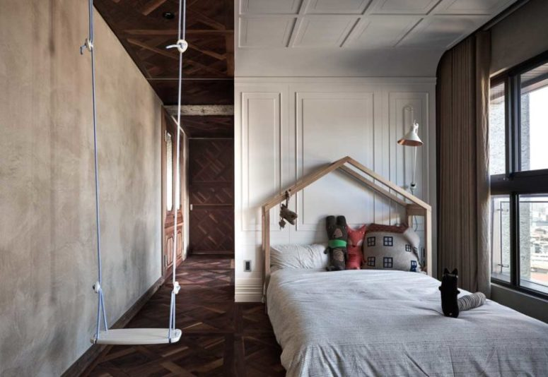 The kids' room is done with a swing, a house-shaped bed and concrete and molding walls