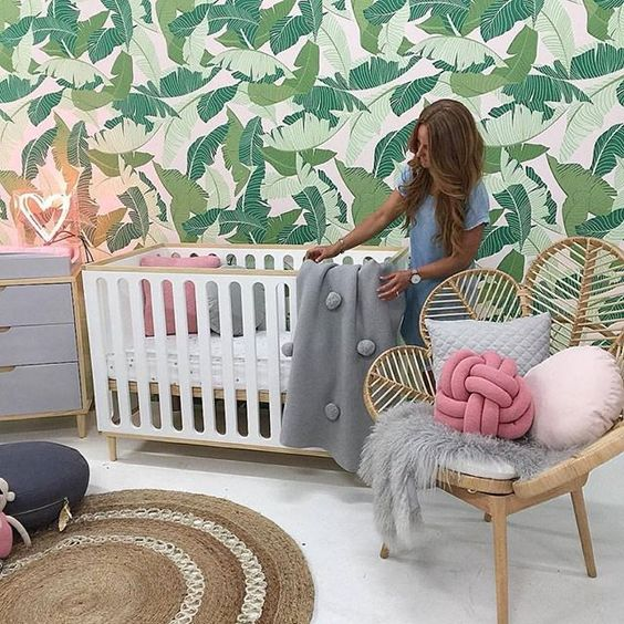 a fun tropical nursery with a tropical leaf statement wall, a rattan chair, a crib, a jute rug and a neon light