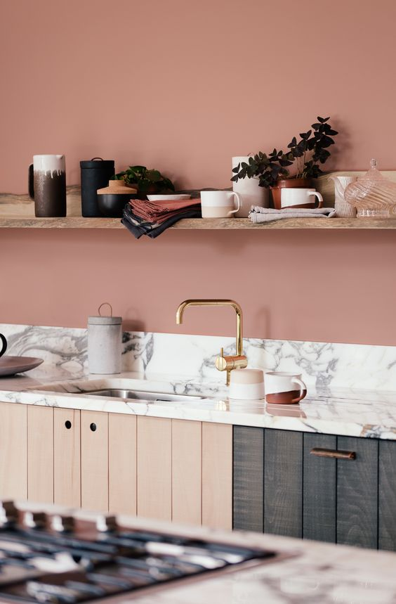 a terracotta pink kitchen with open shelving, wood plank cabinets and a white marble backsplash and countertop