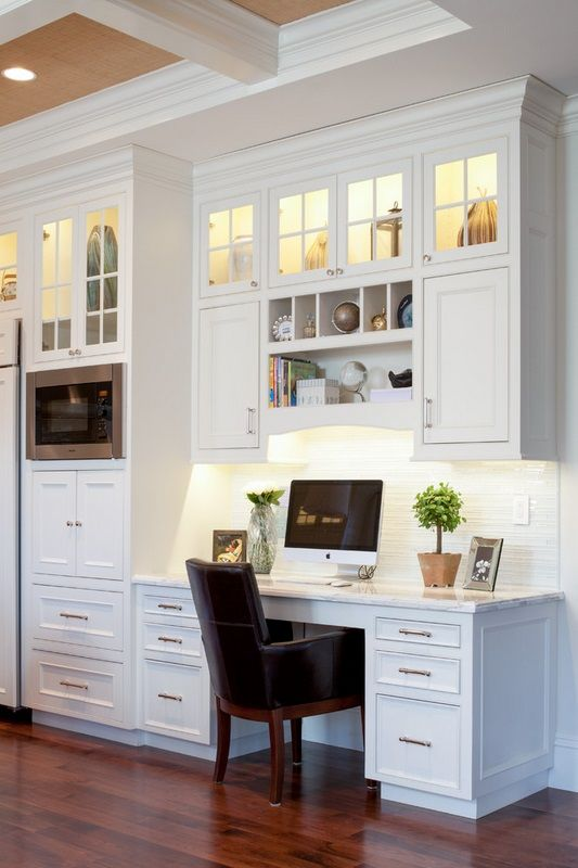 a white farmhouse kitchen with a seamless office nook with built-in lights and a large comfy desk