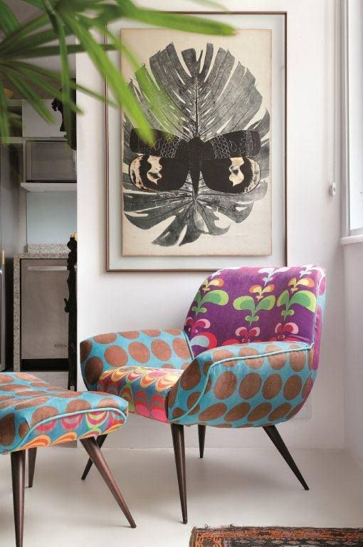 a colorful mid century modern chair with different armrests, a seat and a back plus a matching footrest
