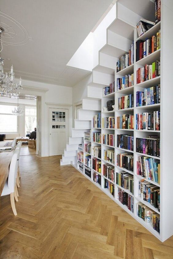 a large bookcase built under the stairs is all you need to save the space and acomodate them all