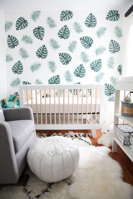 a leaf print wall, faux fur, a white leather ottoman and lots of natural light for a clean look