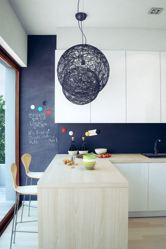 a modern white kitchen with a chalkboard backsplash and light-colored wood that make it more special