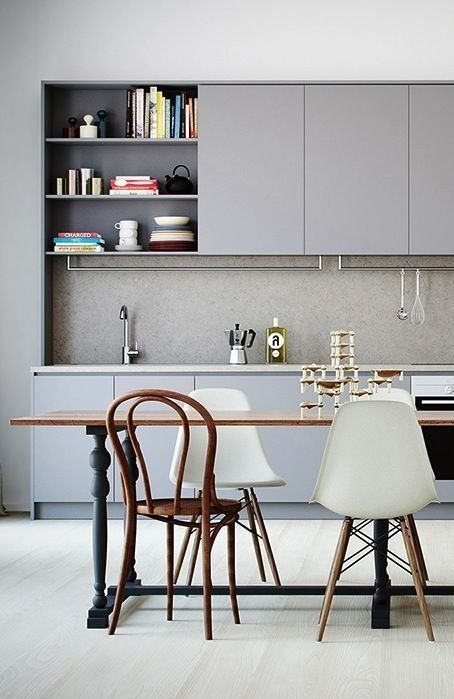 a monochrome grey kitchen is perfectly completed with a raw concrete backsplash that makes it cooler