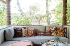 10 a screneed porch with a striped corner couch, a lantern, a side table and much greenery