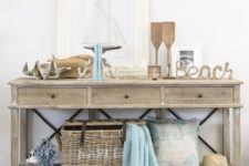 10 a wooden console with oars, shells, driftwood, rope, artworks and a basket for storage