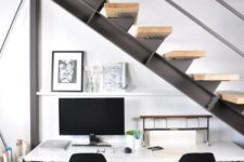 an industrial shared workspace with a metal and wood staircase that doesn't prevent light from coming inside