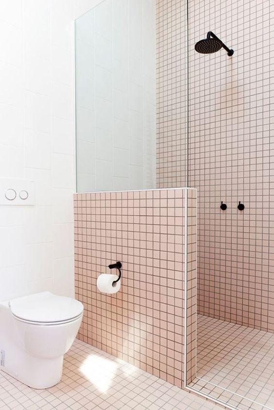 light pink tiles are highlighted with black grout and contrasting white touches