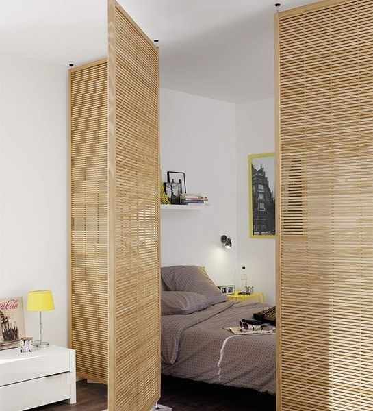 wood lattice doors gently separate the sleeping zone from the rest of the open layout letting light in