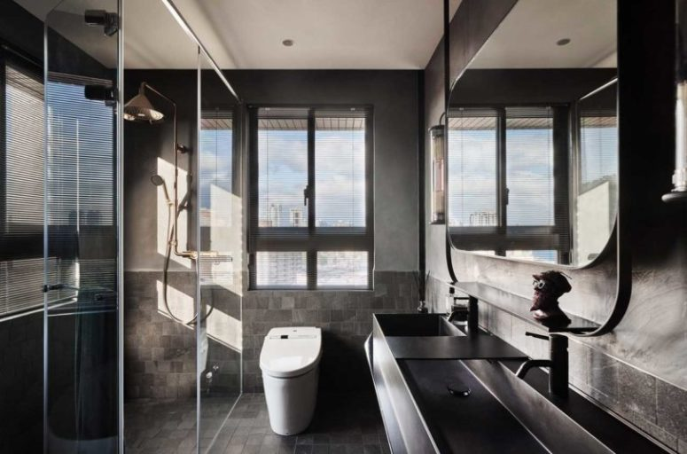 The bathroom is done in more industrial style, with grey tiles and metal sinks