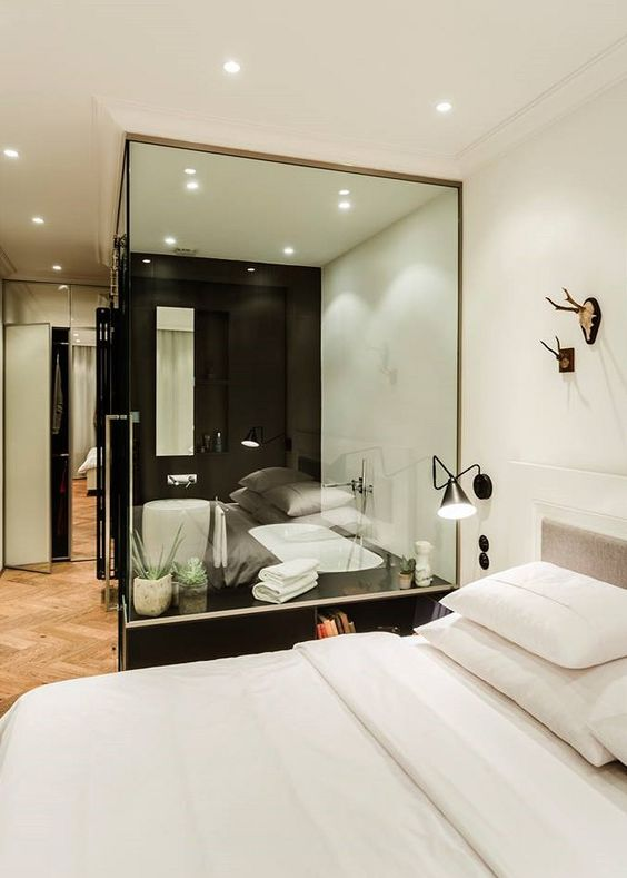 a black and white contemporary bedroom with a bathtub in a glass cube to integrate it into the decor