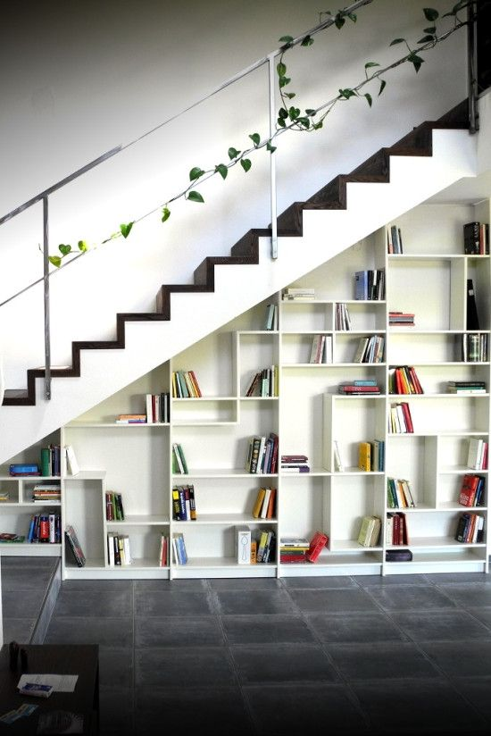 a built-in bookcase with geometrically placed shelves and books becomes a cool decor feature