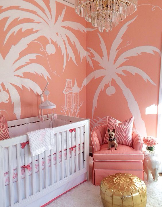 a colorful glam nursery with pink tropical print walls, a pink chair, a glam chandelier and a shiny ottoman