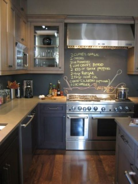 a navy kitchen with grey countertops and a chalkboard backsplash to chalk down the recipes