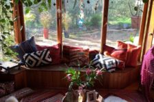 11 a screened boho porch with a built-in wooden bench, faux fur, hanging greenery and lanterns