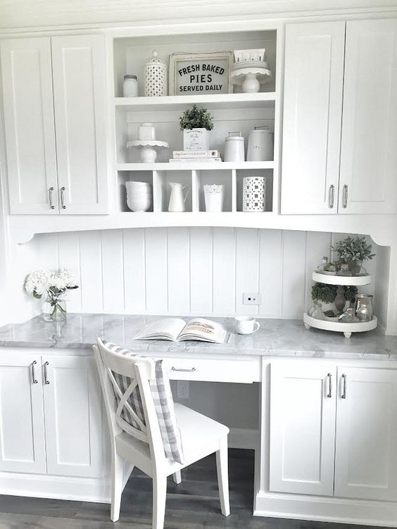 a vintage inspired white kitchen with a seamlessly built in desk with a marble countertops