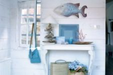 11 a whitewahsed entryway with a small table, a fish figurine, baskets, driftwood and corals for decor