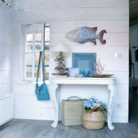 a whitewahsed entryway with a small table, a fish figurine, baskets, driftwood and corals for decor