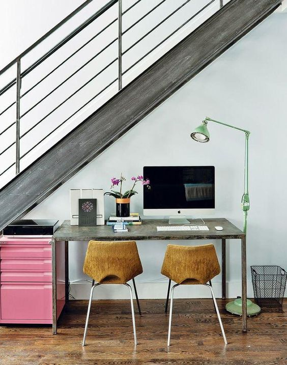 a wood and metal staircase lets light in and a green floor lamp adds more light