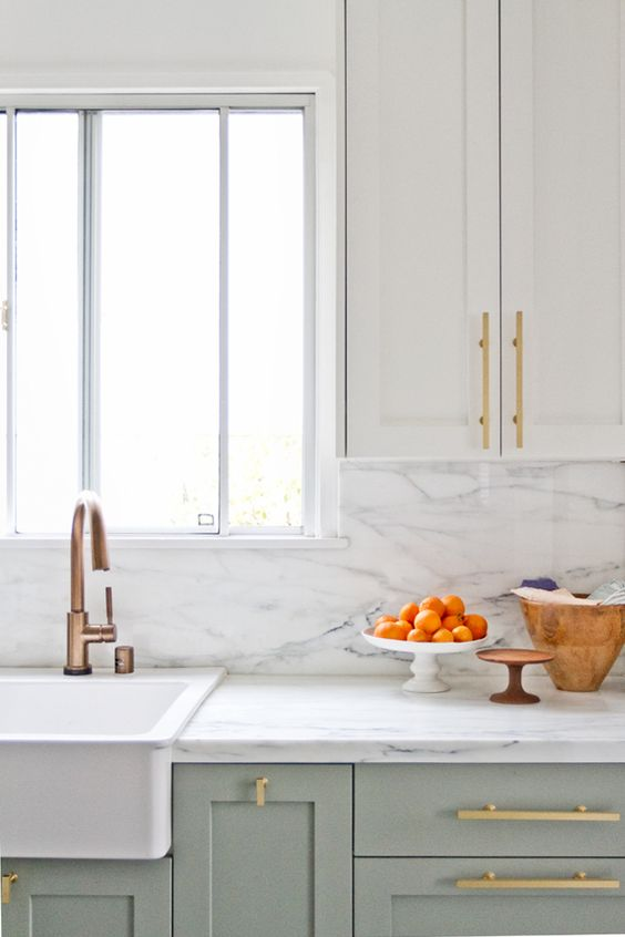 cream and light green cabinets with gilded handles and a white marble backsplash for a chic and refined accent