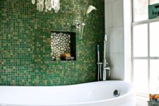 11 glossy green and gold glitter little tiles for an accent wall, mother of pearl chandelier create a glam space