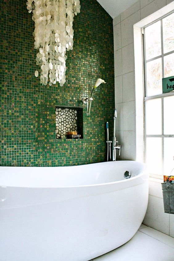 glossy green and gold glitter little tiles for an accent wall, mother of pearl chandelier create a glam space