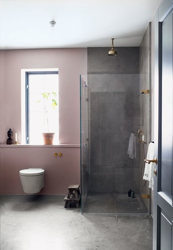 the contrast between pink walls and grey concrete is striking and the space doesn't look too glam and girlish