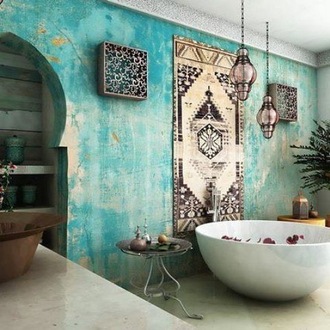a Moroccan styled bathroom with a watercolor turquoise wall, lanterns and other details
