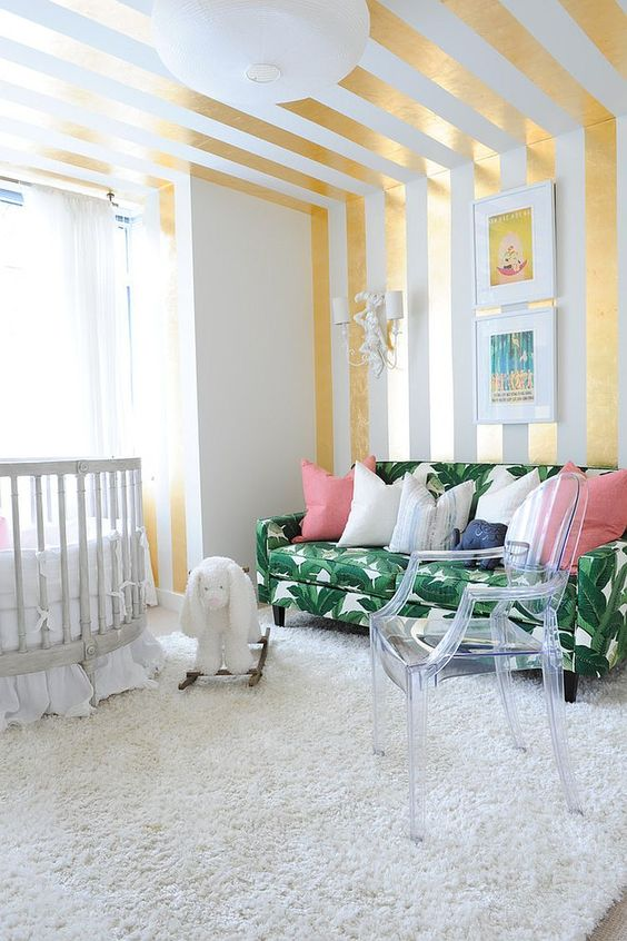a bright nursery with a glam feel, a striped gold and white wall and ceiling, a tropical leaf print sofa and an acrylic chair