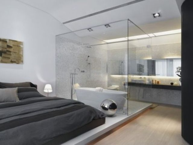 a contemporary bedroom with a bathtub separated with a glass divider and a sink stand behind it