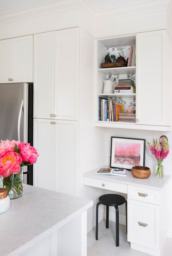 a contemporary kitchen in white with a small home office nook with drawers and a cabinet