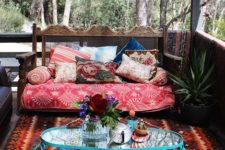 12 a gypsy-styled porch with a bright printed rug, a colorful bench and a blue forged side table