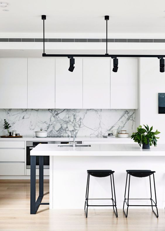 a monochromatic space in black and white with a white marble backsplash and black lights for a deeper look
