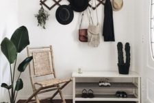 a simple shoe shelf, a woven chair, a geometric hanger on the wall and a geo rug