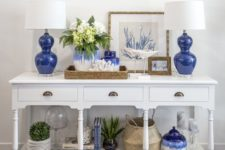 12 a white vintage console with bold blue lamps and vases, plants in pots, baskets and corals