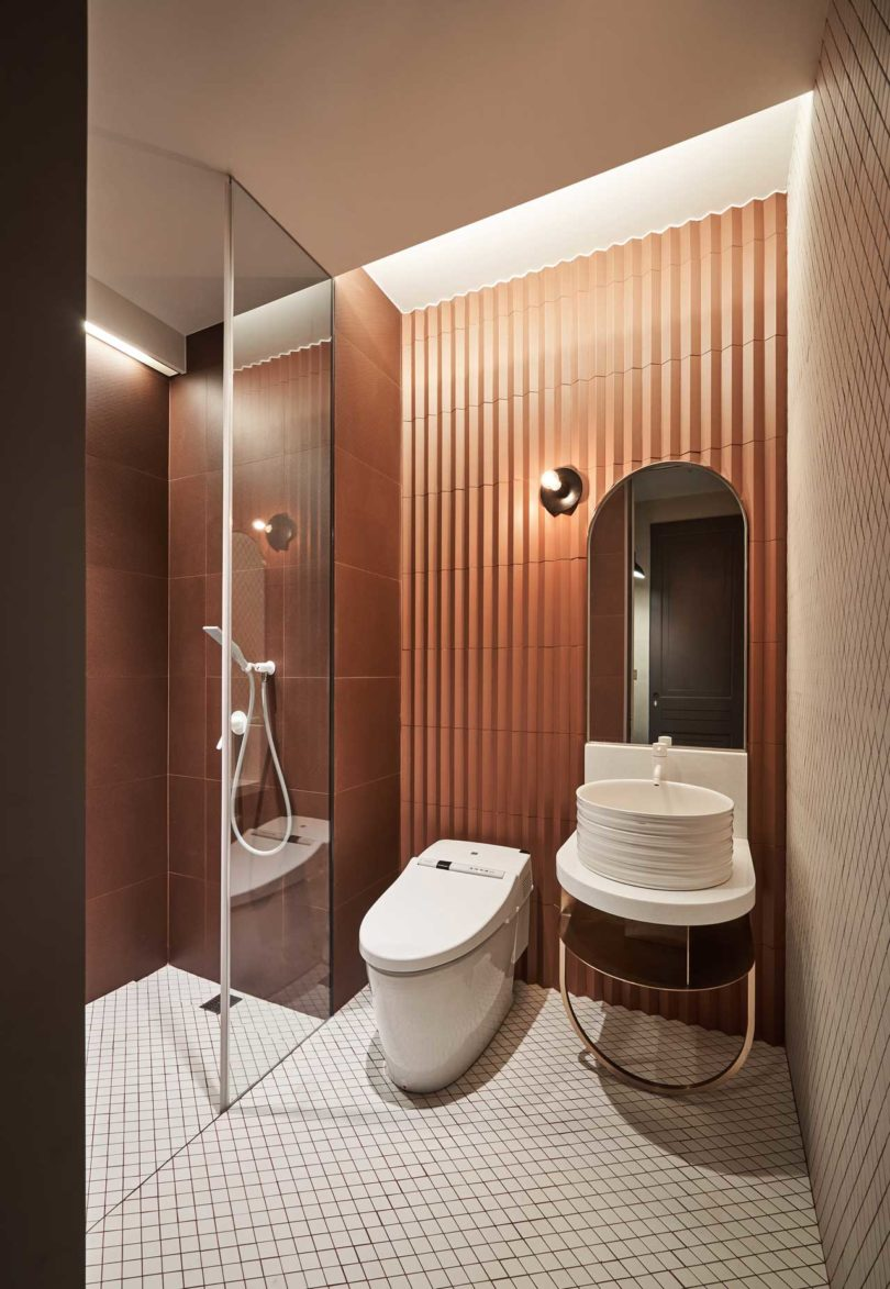 The second bathroom is very catchy, done in orange and rust shades