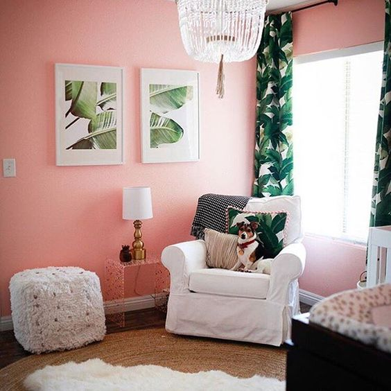 a girl's nursery with pink walls, a crystal chandelier, faux fur and tropical leaf artworks and textiles