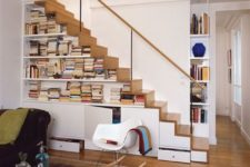 13 a modern staircase that features cabinets for storage and open bookshelves