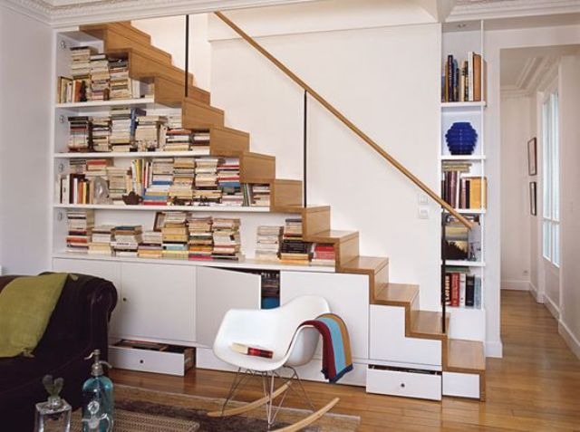 a modern staircase that features cabinets for storage and open bookshelves