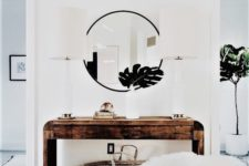 13 a rough wood console table, a round mirror, a faux fur stool and tropical leaves