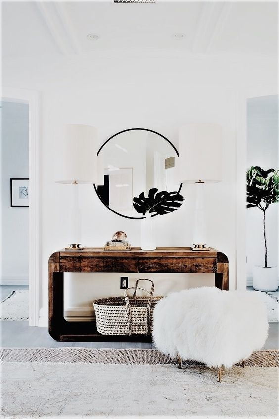 a rough wood console table, a round mirror, a faux fur stool and tropical leaves