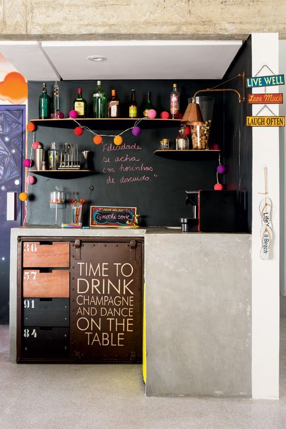 a small modern kitchen with concrete covered cabinets and chalkboard walls instead of backsplashes for a modern look