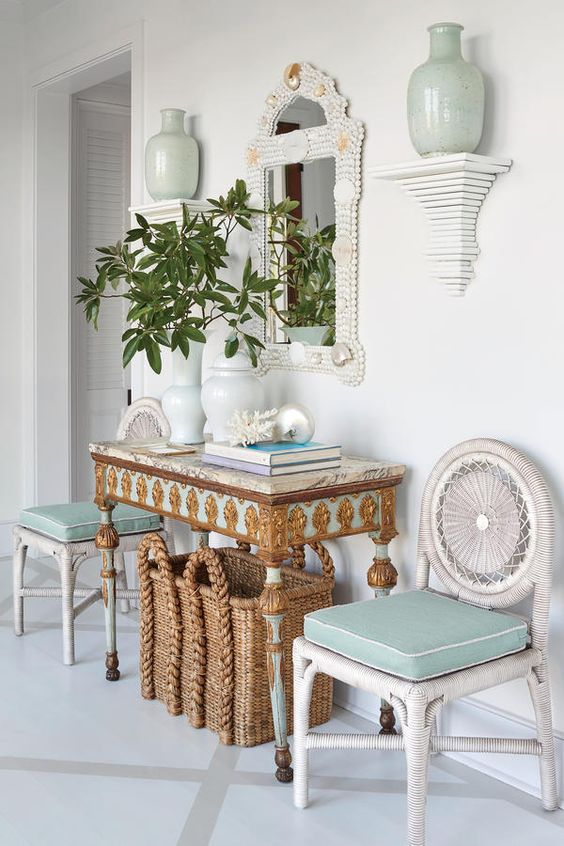 a whimsy and luxurious beach entryway with aqua touches, a basket for storage, white woven chairs, an encrysted console and a shell clad mirror