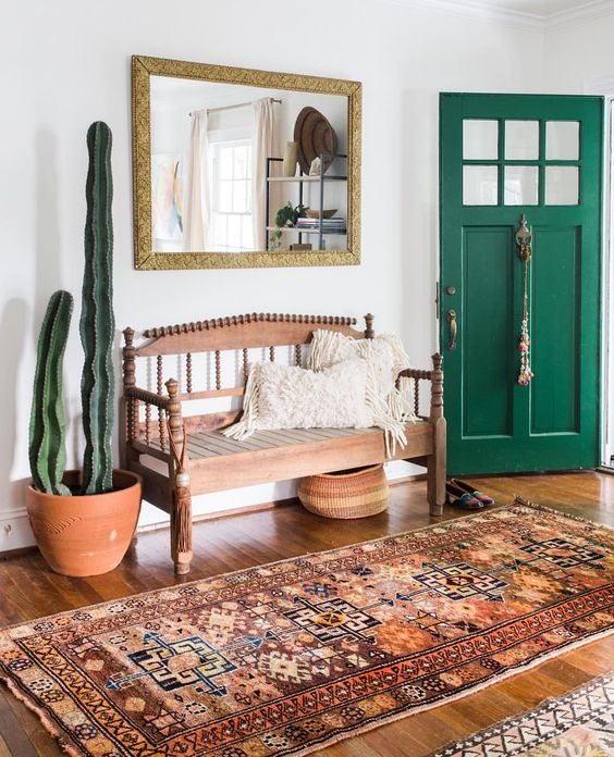 a boho rug, a vintage wooden bench, cacti and a mirror ina  gilded frame