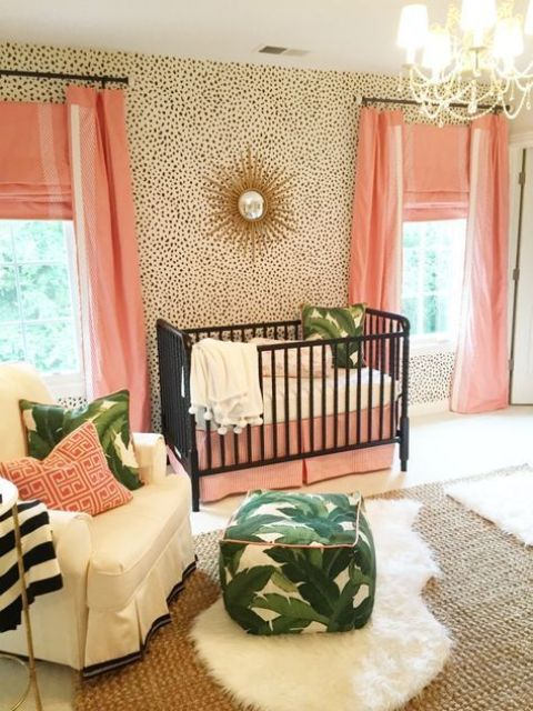 a glam tropical nursery with dalmatin print walls, pink textiles, black cribs and leaf print accessories
