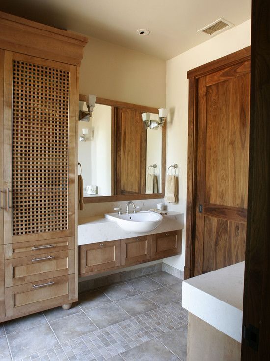 a large wardrobe with wood lettice doors brings a relaxed and vacation feel to the bathroom